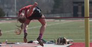 Lawrence High's Katie Lomshek clears the bar in the high jump during a meet Thursday, March 28, 2013, at LHS.
