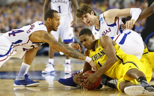 Kansas players Travis Releford, left, and Jeff Withey scramble for a tie up with Michigan forward Glenn Robinson III during the second half on Friday, March 29, 2013 at Cowboys Stadium in Arlington, Texas.