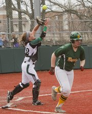 Free State sophomore catcher Paige Corcoran looks to pull down an out on Shawnee Mission South's Hayden Roberts (5) on Saturday, March 30, 2013, at FSHS.