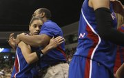 Kansas University guard Angel Goodrich gets a hug from an assistant coach near the end of the Jayhawks' 93-63 Sweet 16 loss to Notre Dame on Sunday in Norfolk, Va.