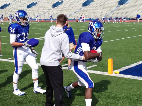 KU running back Tony Pierson takes a handoff from Charlie Weis Jr., during Tuesday's practice at Memorial Stadium.