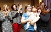 Smiles and applause fill the room as school bond issue supporters celebrate their victory shortly after the results were shown on the big screen of the Alton Ballroom at Pachamama's. Pictured from left are Nancy Hamilton, Adina Morse, Vanessa Sanburn with her three-month-old daughter, Amelia Lowen and Jennifer Osborn. Sanburn and Morse were the top two vote getters in the school board race, respectively. Nick Krug/Journal-World Photo