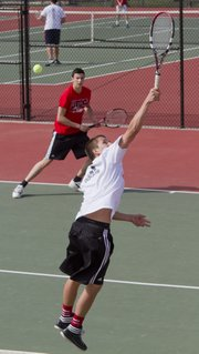 Lawrence High's Austin Abbott, foreground, reaches high for a backhand shot during the Lions No. 1 doubles match Tuesday, April 2, 2013, at LHS against Bonner Springs. Abbott and his partner Christoph Brandt, background left, won the match, 8-6.