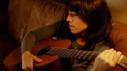 "Stephanie Zuluaga, an opera singer from Overland Park, holds the titular guitar in a scene from ""Esta Guitarra Vieja."""
