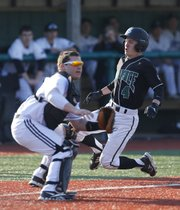 Free State runner Joel Spain slides in to tie the game behind Olathe Northwest catcher Luke Knight in the third inning on Thursday, April 4, 2013, at Free State High School.