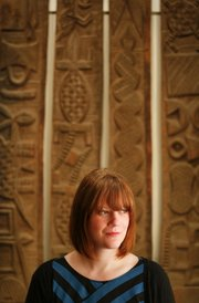 Casey Mesick was recently hired by the Spencer Museum of Art for her expertise in ethnographic collections. She is pictured before a set of four door panels from the Nupe culture in Nigeria.