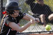 Lawrence High's Katie Murrish (12) lays down a bunt against Shawnee Mission East Thursday, April 4, 2013 at LHS.