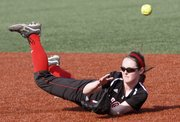 Lawrence High second baseman Kenzie Garvin hits the ground attempting to reach an infield hit in the Lions' doubleheader split with Shawnee Mission East on Thursday, April 4, 2013 at LHS.
