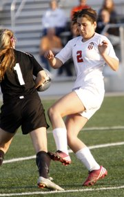 Lawrence High's Sadie Keller attempts to move the ball past a defender in the Lions' soccer game against Shawnee Mission Northwest on Thursday, April 4, 2013 at LHS.