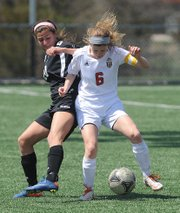 Lawrence's Ella Magerl (6) works a possession against Blue Valley West's Ashlie Elver on Saturday, April 6, 2013, at LHS.