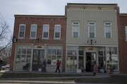 Shoppers peruse store windows at Seventh and Locust streets on a Friday afternoon. The corner is gaining an identity as a destination neighborhood for antiques and home decor, with several stores now open in the historic North Lawrence buildings.
