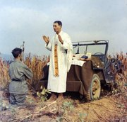 Father Emil Kapaun celebrates Mass using the hood of his jeep as an altar, as his assistant, Patrick J. Schuler, kneels in prayer in Korea on Oct. 7, 1950, less than a month before Kapaun was taken prisoner. Kapaun died in a prisoner of war camp on May 23, 1951, his body wracked by pneumonia and dysentery. On April 11, President Barack Obama will award the legendary chaplain, credited with saving hundreds of soldiers during the Korean War, the Medal of Honor posthumously.