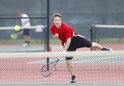 Lawrence High junior Thomas Irick sends a serve over the net to Free State senior Richard Lu during the No. 1 singles match, Tuesday, April 9, 2013, at Lawrence High.