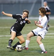 Lawrence High's Gretchen Hierl, right, works for possession against Olathe Northwest's Lisa Landis during the second half, Tuesday, April 9, 2013, at LHS.