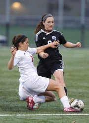 Lawrence High's Sadie Keller, front, fights for a possession with Olathe Northwest's Shelby Mochal during the second half Tuesday, April 9, 2013, at LHS.