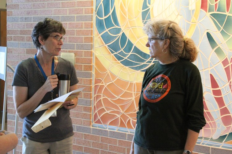 Trish Unruh, left, visits with Nancy O'Connor, director of education and outreach at The Merc, during the first day of the CSA in the lobby of the Community Health Facility, 200 Maine St.