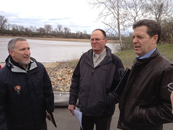 From left to right Brian Leaders of the National Park Service, Roger Wolfe of the Kansas Department of Wildlife, Parks and Tourism, and Gov. Sam Brownback talk Thursday after a news conference held on a boat ramp to the Kansas River.