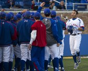 Kansas' Alex DeLeon, right, is congratulated by teammates after blasting a home run to give Kansas the lead during Kansas' game against Texas on Friday, April 12, 2013, at Hoglund Ballpark.
