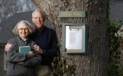 Joe and Vicki Douglas are pictured next to their Poet Tree on April 13. After receiving inspiration from other public poetry posts, Joe Douglas created the box, which rests on the front of a maple tree in their front yard.