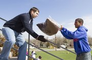 Kansas University sophomore Corey Boucher, St. Louis, Mo., right, tosses a bag of mulch to John Curran, Olathe, at the Lawrence High School football stadium during the third annual Big Event volunteer service day on Saturday. Nearly 3,000 KU students and staff members spread out across Lawrence performing volunteer duties such as mulching, weeding and planting flowers.