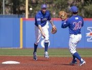 Kansas shortstop Kevin Kuntz, left, tosses the ball to second baseman Justin Protacio for an out at second base during Kansas' game against Texas, Saturday, April 13, 2013, at Hoglund Ballpark.
