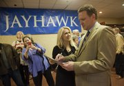 Jennifer Fisher, Miss Kansas 1998, gets an autograph from KU basketball coach Bill Self at the annual KU basketball banquet Monday, April 15,2013, at the Holiday Inn.