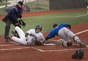 Free State junior Cameron Pope (10) slides past a tag attempt by Leavenworth catcher Zach Harris during their game Monday evening at FSHS.