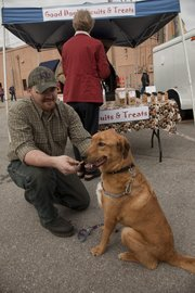 Kevin Larkin gives a dog treat to his dog Dutch at Downtown Lawrence Farmers' Market on Saturday. Good Dog! Biscuits and Treats are made by homeless guests at the Lawrence Community Shelter.