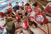 Lawrence High swimmers come together in a team huddle prior to Tuesday's Lawrence Invitational at LHS.