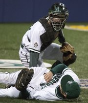 Free State catcher Lee McMahon checks on teammate Sam Hearnen after Hearnen ran into a fence while going after a foul ball during Free State's opening around game against Topeka Hayden in the River City  Baseball Festival Thursday evening at Hoglund Ballpark.