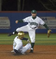 Free State sophomore Cooper Karlin (9) avoids Hayden's Jake Kresin at second base after throwing to first for a double play during Free State's opening around game against Topeka Hayden in the River City  Baseball Festival Thursday evening at Hoglund Ballpark.