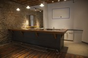 "A 4,000-square-foot cider vinegar factory built in the 1890s at 810 Pennsylvania St. has been renovated and will celebrate its grand opening Friday. The new Cider Gallery features an art gallery and event space — including this bar made with reclaimed wood from the nearby Poehler Lofts building — on the first floor, an ""Entrepreneur Office Hub"" upstairs and an adjacent outdoor event space, which is still under construction."