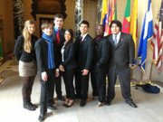 Kansas University students (from left to right) Kate Sopcich, Joey Hentzler, Garrett Wolfe, Gena Pollack, Ramiro Sarmiento, Nelson Ross, and Randy Vidales stand in the Hall of Flags at the Organization of American States headquarters in Washington, D.C., on March 26.