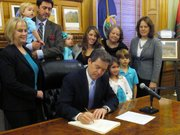 Kansas Gov. Sam Brownback signs a sweeping anti-abortion bill into law during a Statehouse ceremony Friday in Topeka. He is surrounded by legislators, abortion opponents and the family of Michael Schuttloffel, to the left just behind Brownback, a lobbyist for the Kansas Catholic Conference.