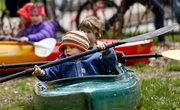 Orris Ihloff Kline, of Lawrence, practices his paddling skills on dry land as he and other kids play in kayaks and canoes provided by Up a Creek Canoe and Kayak Rental during an Earth Day celebration Saturday at South Park. Various local businesses put on demonstrations and provided activities for kids and families around an Earth Day theme.