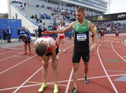 Mile runner Nick Symmonds congratulates Cory Leslie after Leslie took first in the event during the Kansas Relays on Saturday, April 20, 2013 at Memorial Stadium. Symmonds took third behind Leo Manzano. Nick Krug/Journal-World Photo