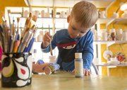 Three-year-old Payton Pringle, Lawrence, concentrates as he paints a car blue at Sunfire Ceramics, 1002 New Hampshire St. Payton was painting the car for a Mother's Day gift.
