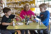Payton Pringle, 3, right, and his brother Dakota, 6, work on painting Mother's Day gifts while their grandmother Kim Wampler works on her own project at Sunfire Ceramics, 1002 New Hampshire St. Wampler and her grandsons live in Lawrence.