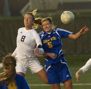 Free State senior Rylee Fuerst (8) and Olathe South's Jaide Allenbrand (5) go after the ball off a corner kick during their game Wednesday evening at FSHS.