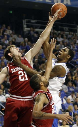 Kentucky's Terrence Jones, right, puts up a shot under pressure from Arkansas' Hunter Mickelson (21) and Marvell Waithe during the first half of an NCAA college basketball game in Lexington, Ky., Tuesday, Jan. 17, 2012.