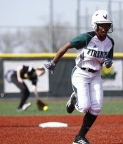 Free State runner A'Liyah Rogers heads toward third as the ball gets through to the outfield during the second inning against Shawnee Mission West on Thursday, April 25, 2013, at Free State High.