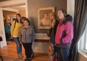 Current and former Kansas University scholarship hall residents Mary Emerson, Keeleigh Smith, Katie Kutsko and Erin Christianson stand next to a portrait of benefactress Elizabeth Miller Watkins that hangs in the KU chancellor's residence, where Watkins used to live.