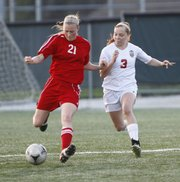 Lawrence High's Addison Campbell chases after Shawnee Mission North's Shayna Thomas during the second half on Tuesday, April 30, 2013 at Lawrence High. Nick Krug/Journal-World Photo