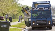 Charles Barnes, operator of one of the city's automated trash trucks, uses a mechanical arm to lift city trash bins off the street in the Prairie Park Neighborhood. The vehicle requires only one crew member.