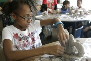 Asjah Harris sculpts an elephant-inspired clay teapot at the Boys and Girls Club of East Heights. Kansas University graduate student Eli Gold led the class in making the teapots and used Asjah's design as the inspiration for a teapot he fabricated in sterling silver.