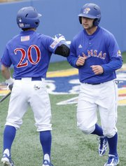 Kansas University infielder Justin Protacio (20) greets Jordan Dreiling at home plate after Dreiling scored on a hit by Ka'iana Eldredge during the Jayhawks' 6-5, walk-off victory against Baylor on Saturday, May 4, 2013, at Hoglund Ballpark.