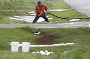 An employee with Haz-Mat Response, Olathe, places a hose to suck up diesel fuel in a ditch Saturday near 106 E. Pearl St. in McLouth. A diesel tanker was resupplying a BP gas station's diesel tank Friday night at 101 E. Lake St., also known as Kansas Highway 16, when over a thousand gallons of diesel spilled onto the ground and into a nearby neighborhood. Residents of two homes on E. Pearl Street voluntarily evacuated their home because of the smell.