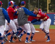 Kansas' Jordan Dreiling, right, is mobbed by teammates after driving in the game winning run in the 10th inning in Kansas' game against Baylor Sunday, May 5, 2013, at Hoglund Ballpark.