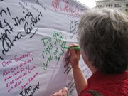 Cinda Schneweis, of Lawrence, writes her message to Gov. Sam Brownback during a rally Wednesday outside the Statehouse. The rally was in support of leaving in place the current system of providing long-term care services for those with developmental disabilities.