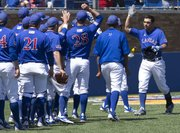 Kansas' Alex DeLeon, right, is congratulated by teammates after hitting a home run during Kansas' game against Kansas State, Saturday at Hoglund Ballpark.
